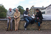 Elderly couplerest on a Cambridge wall as a younger, Asian man and European woman eat food.