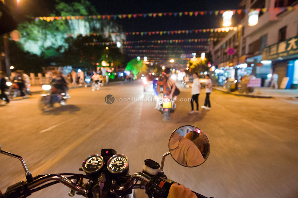 Point of view image of a riding a motorcycle at night on a street in Yangshuo, China.