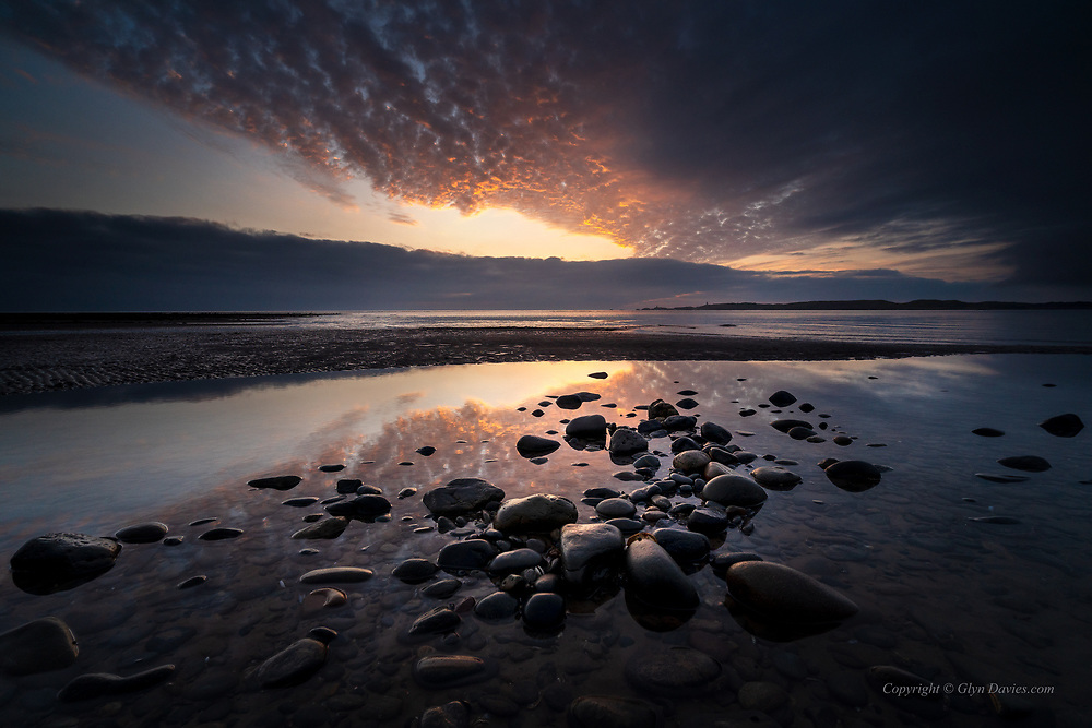 As the fog cleared, a beautiful and gentle sunset appeared, illuminating the calm sea on a slowly incoming tide.
