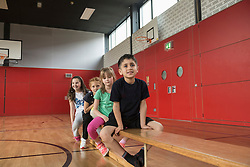 Children resting on bench before exercises in large gym of school, Bavaria, Munich, Germany