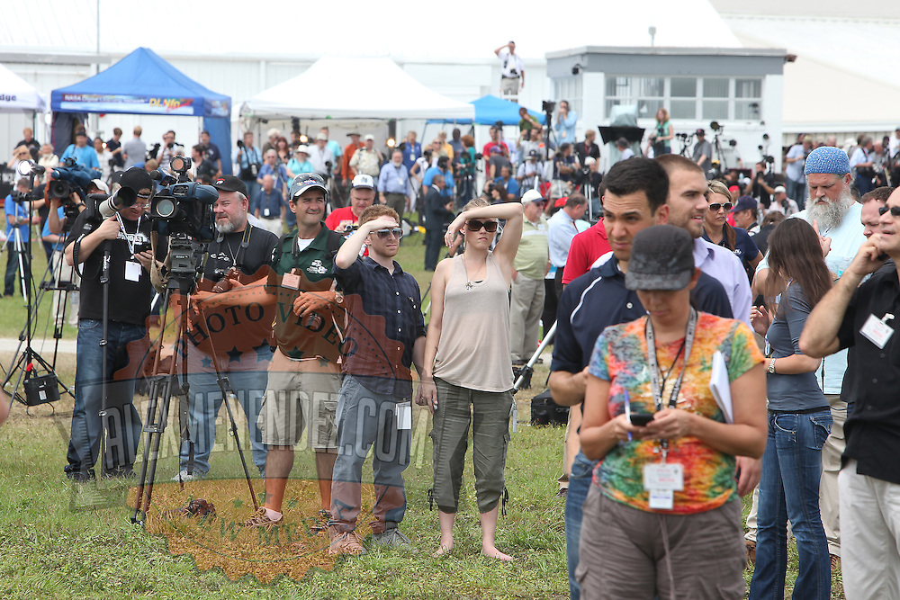 Members of the media react after watching the Space Shuttle Atlantis lift off from the Kennedy Space Center Friday, July 8, 2011, in Cape Canaveral, Fla. Shuttle Atlantis is the 135th and final space shuttle launch for NASA..  (AP Photo/Alex Menendez)