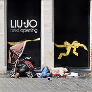 Frankrijk, Lille, 18-8-2013Het kledingmerk Liu Jo opent binnenkort een nieuwe winkel in deze stad. Een Roma vrouw ligt op straat voor het pand te slapen en bedelen met haar kinderen.Lille ligt in een sterk de verarmde regio noordwest. Het is de hoofdstad van Frans Vlaanderen, van de regio Nord Pas de Calais en van het Noorder departement.Foto: Flip Franssen/Hollandse Hoogte