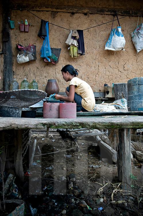 A young girl on a stilt deck washes some dishes. Reungao ethnic tribe. Kontum plateau, Pleiku area, Vietnam, Asia