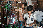 Dhaka, Bangladesh. Boys working in a factory making door mats out of old shoe laces. The children are not disabled but without any formal education and CSID try to convince them to join informal education. Centre for Services and Information on Disability (CSID) is a charity working for integrating disabled children into mainstream society. Boys working in a factory making door mats out of old shoe laces. The children are not disabled but without any formal education and CSID try to convince to join informal education.