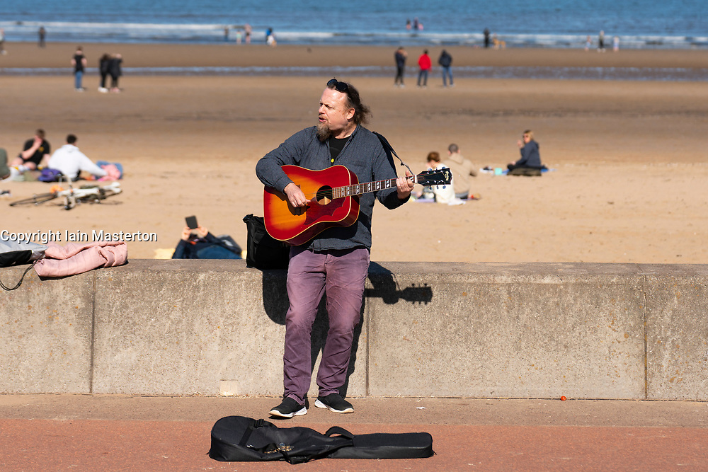 Portobello, Scotland, UK. 3 April 2021. Easter weekend crowds descend on Portobello beach and promenade to make the most of newly relaxed  Covid-19 lockdown travel restrictions and warm sunshine with uninterrupted blue skies. Pic;  Buskers have returned. Iain Masterton/Alamy Live News