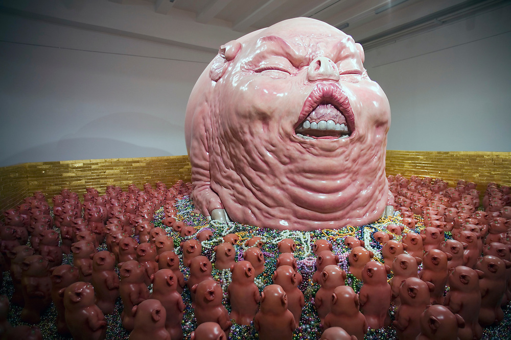 "Visitors to Chen Wenling's exhibition called ""The God of materialism"" look at a sculpture on display at an art gallery in Beijing fashionable 798 art district. A sculpture by Chen Wenling's called ""The God of Materialism""  on display at an art gallery in Beijing fashionable 798 art district."