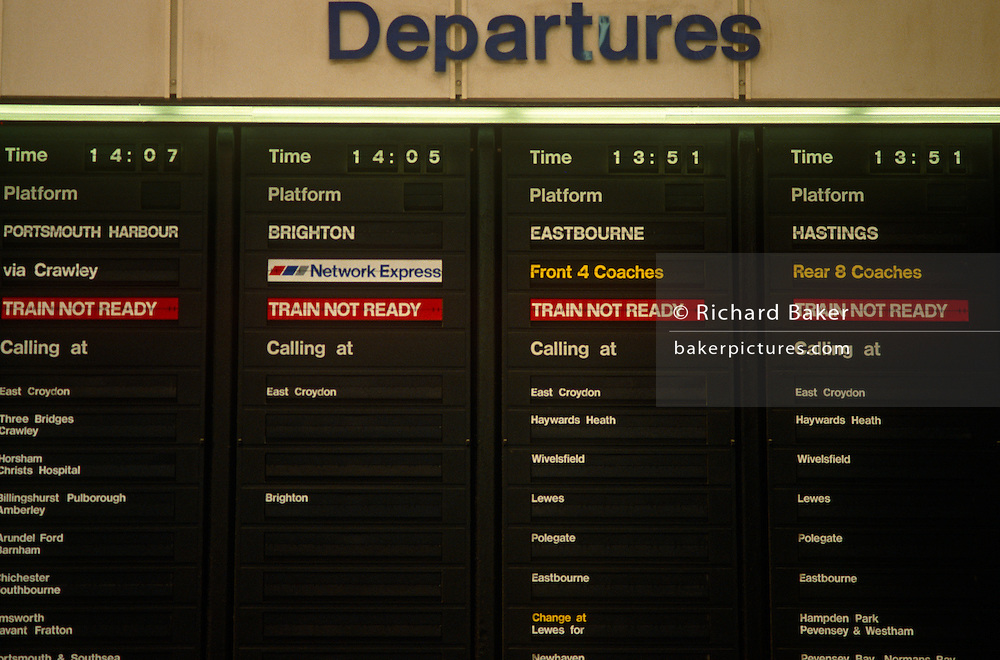 A 90s departures board displays the times and destinations of rail services heading south from this London station hub. Routes to the south coasts towns of Brighton, Eastbourne and Hastings departing in the afternoon from the capital. The Train Not Ready signs are also displayed telling passengers that carriages have yet to be designated and their platforms unallocated.