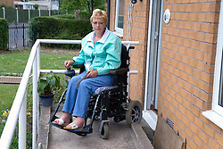Woman wheelchair user leaving her house using a concrete ramp,