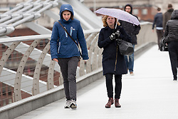 © Licensed to London News Pictures. 27/01/2016. London, UK. People walk over Millennium Bridge in central London during wet and windy weather. Storm Jonas continues to bring rain and gales to the UK today.  Photo credit : Vickie Flores/LNP
