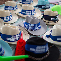 Sombreros with messages supporting Juan Orlando Hernández on sale during a march to support the President. Daily demonstrations against the President were made amid the widespread belief that the president has used fraud to hold onto power. Videos circulated of people being paid to attend to pro-government march.