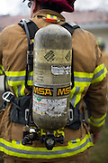 A fire fighter wears an oxygen tank as multiple fire departments, including Milpitas Fire Department, Spring Valley Fire Department, and Cal Fire, work to contain and extinguish a structure fire at the 3000 block of Calaveras Road near Spring Valley Golf Course in Milpitas, California, on February 10, 2014. (Stan Olszewski/SOSKIphoto)