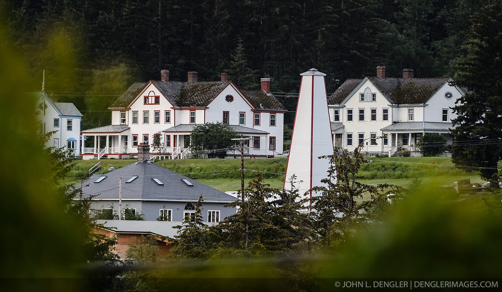 """After being absent from the historic Fort Seward skyline since approximately the 1930s, the 60-foot tower of the fort's fire hall has been restored to its original height. The building and tower, built around 1904 in Haines, Alaska, was shortened to approximately half its height in the 1930s for unknown reasons. The restoration included rebuilding a missing 35-foot section of the 60-foot tower whose purpose was to dry fire hoses. The tower restoration was completed by building its four sections on the ground and then hoisting those sections with a crane into place on top of each other.<br /> <br /> Through the years, the historic Fort Seward area, a former U.S. Army post, has been referred to as Fort William H. Seward, Chilkoot Barracks, and Port Chilkoot. The National Historic Landmarks listing record for the fort says that """"Fort Seward was the last of 11 military posts established in Alaska during the territory's gold rushes between 1897 and 1904. Founded for the purpose of preserving law and order among the gold seekers, the fort also provided a U.S. military presence in Alaska during boundary disputes with Canada. The only active military post in Alaska between 1925 and 1940, the fort was closed at the end of World War II."""" <br /> <br /> The bottom portion of the fire hall is being leased as commercial space. Due to fire code restrictions there is no public access to the upper portion of the tower. <br /> <br /> The fire hall was restored over a two-year period by owners Joanne Waterman and Phyllis Sage who also own the fort's original guardhouse located next door to the fire hall. That building, now known as the Alaska Guardhouse, is a bed and breakfast."""