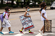 Charleston, United States. 31 May, 2020. Young protesters walks across a street holding signs following a peaceful demonstration over the death of George Floyd, along the historic Battery May 31, 2020 in Charleston, South Carolina. Floyd was choked to death by police in Minneapolis resulting in protests sweeping across the nation.  Credit: Richard Ellis/Alamy Live News