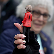 A supporter holds a signed figurine of Democratic presidential candidate Elizabeth Warren at a polling station at Amherst Street Elementary School in Nashua, N.H., on Tuesday, February 11, 2020.
