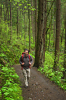 Male hiker with red backpack on trail in Columbia River Gorge National Scenic Arae, Oregon