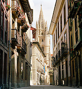 The spire of San Salvador Cathedral towers above a narrow shopping street in Oviedo, Asturias, Spain