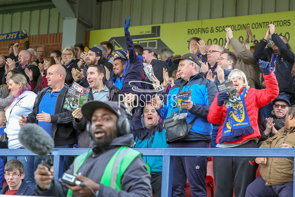 AFC Wimbledon fans clapping during the EFL Sky Bet League 1 match between AFC Wimbledon and Gillingham at the Cherry Red Records Stadium, Kingston, England on 23 March 2019.