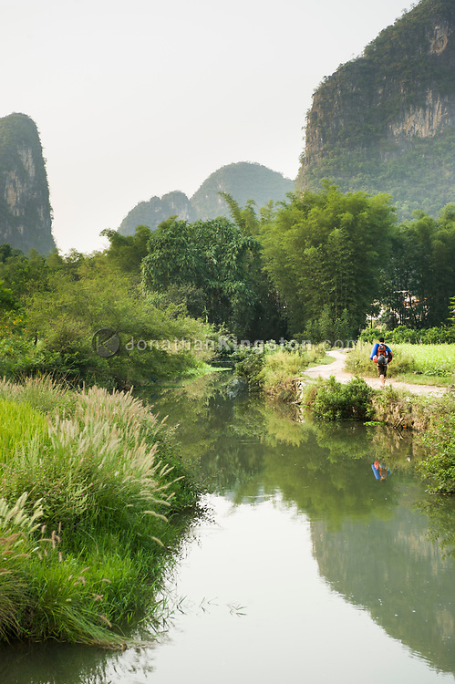 A man wearing a backpack walks down a gravel road next to a river near Yangshuo, China  (Model Released, Sean Ouyang).