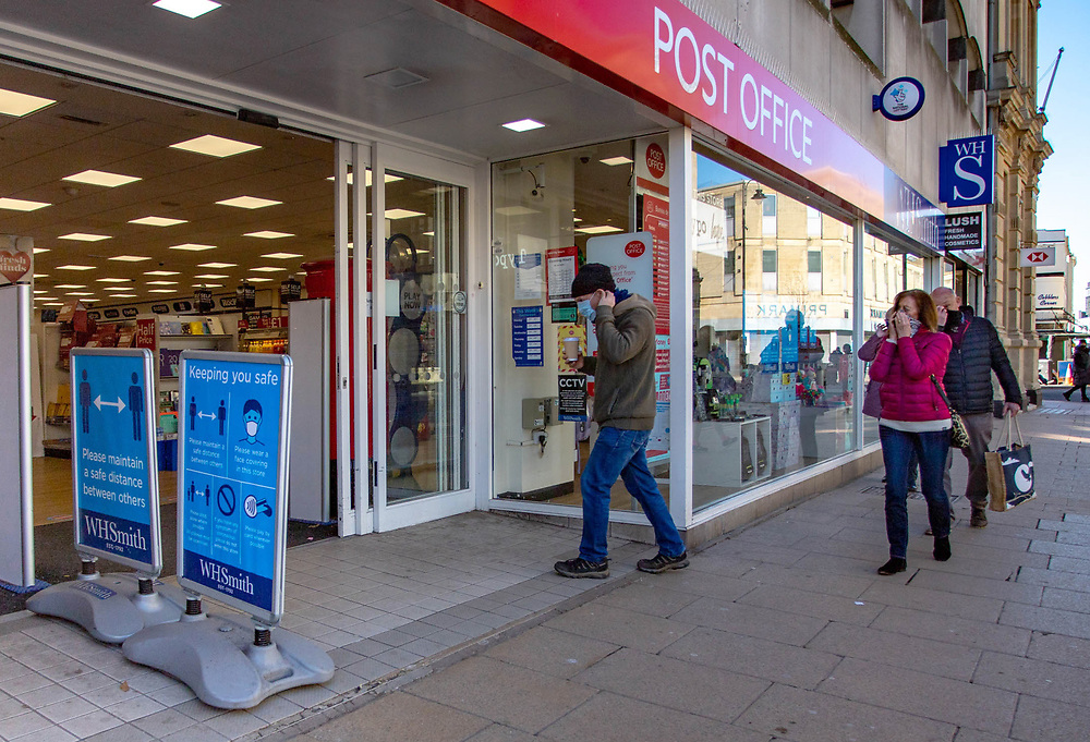 25th February 2021.Shoppers prepare their PPE before entering a post office during the third national lockdown in Cheltenham High Street.