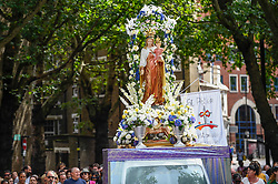 © Licensed to London News Pictures. 21/07/2019. LONDON, UK.  People take part in the Procession of Our Lady of Mount Carmel, starting at St Peter's Italian Church and then around the streets of Clerkenwell.  Floats carry life size depictions of Biblical scenes in a Catholic festival which has taken place annually for 100 years in the area which was once the capital's Little Italy.  Photo credit: Stephen Chung/LNP