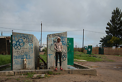 """Nadine Wilskut, 14, stands near some vandalized ablution facilities in Jamestown, which is located in the Cape Winelands, one of the districts in the Western Cape that has been designated a hotspot area, in terms of people testing positive for COVID-19.<br /> """"It's not a good situation because I can't go to school,"""" she says. """"I'm stuck here at home, watching television, playing games. That's all. …<br /> """"The Corona affected some people. They don't have enough food. They lost their jobs. They can't afford to buy medicine,"""" she says. <br /> When South Africa moves down to Stage 3 of the nationwide lockdown on June 1st, hotspot areas will remain under stricter regulations and surveillance, per the latest government announcements. PHOTO: EVA-LOTTA JANSSON"""