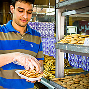 Baker in Nasr City prepares biscuits for a customer. During the revolution, bakeries often worked overtime to keep up with demand as people feared ingredient scarcity. Cairo, Egypt.