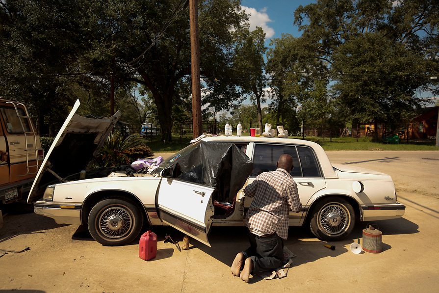 """Mike Taylor, 59, drains water from the gas line in his car in the aftermath of tropical storm Harvey in Acres Homes, Houston, Texas, U.S. September 10, 2017. """"I got it bad, I'm so hot and tired,"""" said Taylor."""