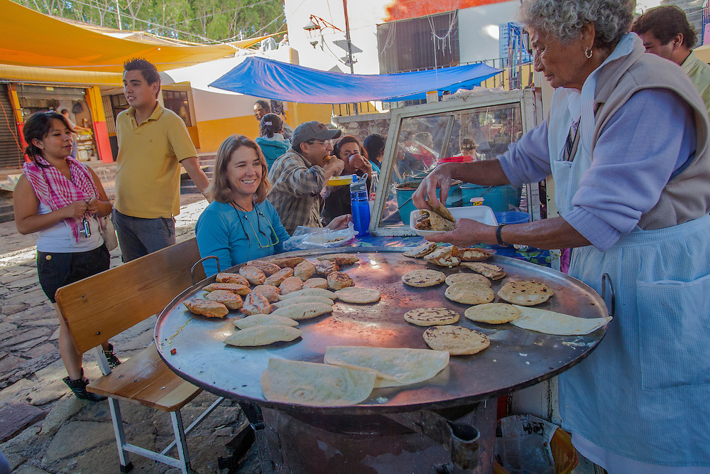 North America, Mexico, Guanajuato State, Guanajuato,  Outdoor restaurant in market with tlacoyos (oval shaped fried or toasted cakes made of masa)  and other food cooking on hot comal.