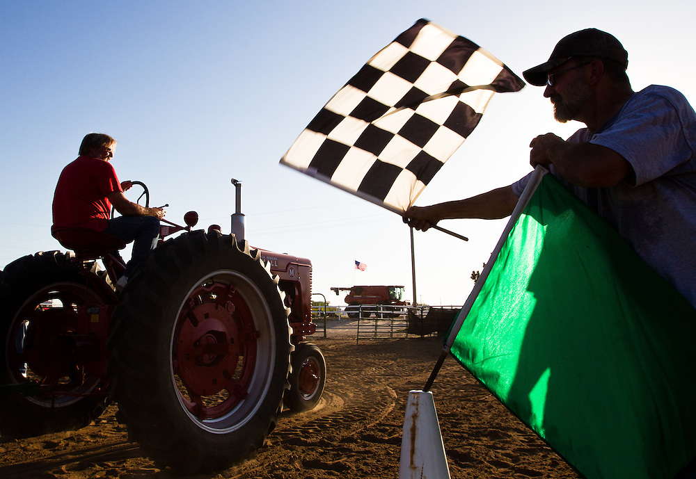Gary Lassen waves the checkered flag as a competitor crosses the finish line during the Antique Tractor Games Thursday evening in the Open Air Arena at the Nebraska State Fair in Grand Island. (Independent/Matt Dixon)