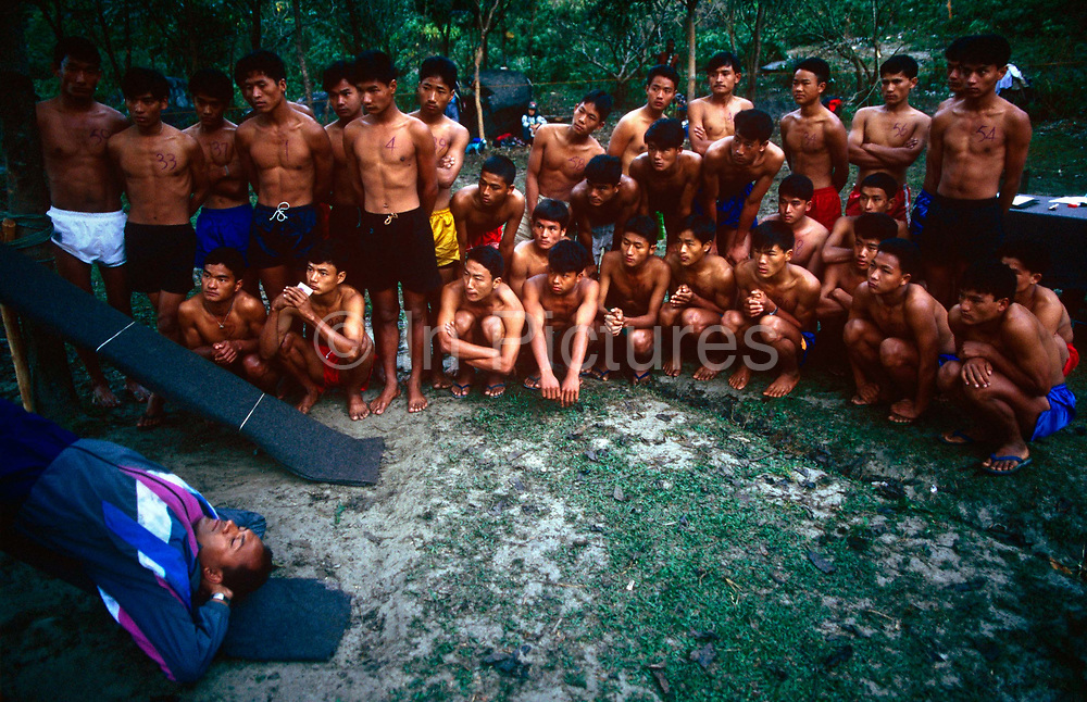 Young Nepali boys watch how to perform sit-ups in Himalayas, hoping to be recruited for the Gurkha Regiment. This is part of a tough endurance series to find physically perfect specimens for British army infantry training. They will need to perform 25 straight-kneed sit-ups at a 45° slant both within 60 seconds to pass. 60,000 boys aged between 17-22 (or 25 for those educated enough to become clerks or communications specialists) report to designated recruiting stations in the hills each November, most living from altitudes ranging from 4,000-12,000 feet. After initial selection, 7,000 are accepted for further tests from which 700 are sent down here to Pokhara in the shadow of the Himalayas. Only 160 of the best boys succeed in the journey to the UK. The Gurkhas have been supplying youth for the British army since the Indian Mutiny of 1857.