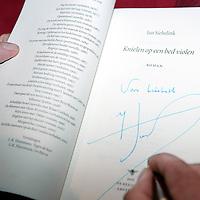 """Nederland,Apeldoorn ,13 december 2005..Schrijver Jan Siebelink is te gast voor een interview bij Podium Gigant en signeert in de pauze en achteraf zijn laatste roman """"Knielen op een bed violen"""".Handtekening."""