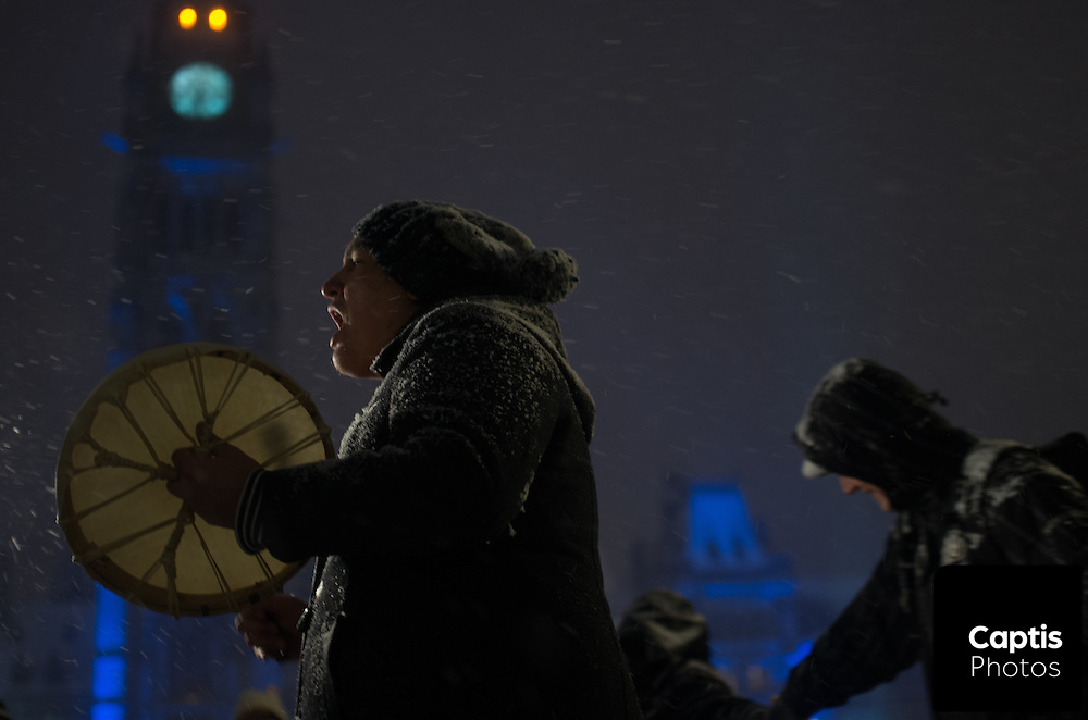 """A man beats a drum on Parliament Hill during a drum circle. The drum circle was held to commemorate the second anniversary of the """"Idle No More"""" movement. December 10, 2014. CAPTIS PHOTOS/Brendan Montgomery"""