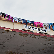 Clothes hanging between the flag masts of Idomeni railway station. Many families have moved in the old train station since the main transit camp is overcrowded. <br /> <br /> Thousands of refugees are stranded in Idomeni unable to cross the border. The facilities are stretched to the limit and the conditions are appalling.