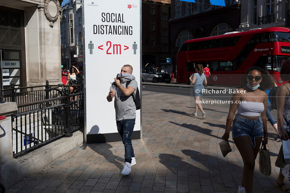 With a further 184 reported UK Covid deaths in the last 24 hrs, a total now of 43,414, a man with his jumper wrapped around his mouth and nose walks through Oxford Circus where a post advises Londoners to observe the correct two metre social distances, during the Covid pandemnic lockdown, now easing after three months of the Stay At Home policy but now being relaxed as the shops re-open, on 26th June 2020, in London, England. Government restrictions on the 2 metre rule is to be realxed on 4th July and replaced with 'one metre plus' in the hope it stimulates the struggling UK economy.
