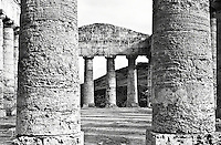 greek temple of Segesta in Sicily, italy. View of interior through two columns on foregournd. Black and white picture
