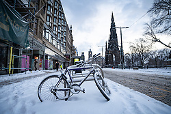 Edinburgh, Scotland, UK. 10 Feb 2021. Big freeze continues in the UK with heavy overnight and morning snow in the city. Pic; Snow covered bicycle on Princes Street.  Iain Masterton/Alamy Live news