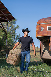 hot young cowboy with hay on a ranch