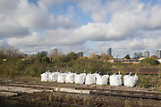 Aggregates and construction materials lined up at the trackside, seen through the window of a Southern train carriage window, on 7th November 2019, in London, England