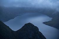 Summer sea fog hangs low in sky over Kirkejord, viewed from Reinebringen, Moskenesøy, Lofoten Islands, Norway