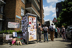 © Licensed to London News Pictures. 17/06/2017. London, UK.  Member of the public look at tributes and missing posters in front of  Grenfell tower block (pictured right) in west London following a devastating fire earlier this week. The blaze engulfed the 27-storey building killing 12 - with 34 people still in hospital, 18 of whom are in critical condition. The fire brigade say that they don't expect to find anyone else alive. Photo credit: Ben Cawthra/LNP
