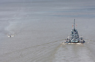 Highland, New York - The USS Slater moves past the Walkway over the Hudson on its way north on the Hudson River on June 30, 2014. The Slater served in World War II and is the last destroyer escort vessel afloat in America. The Slater was on the way to Albany, N.Y., to resume its duties as a floating museum. The tugboats Frances, left, and Margot, assisted the Slater.
