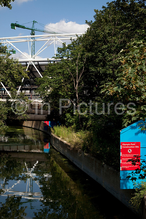 Security barrier and warning signs at the edge of the 2012 Olympic site in East London. This area of Hertford Union Canal runs alongside the main stadium area.