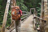 Backpacker on Suspension Bridge over Canyon Creek, Suiattle River Trail, Glacier Peak Wilderness North Cascades Washington