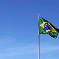 South America, Brazil, Brasilia.  The flag of Brazil waves against a blue sky.