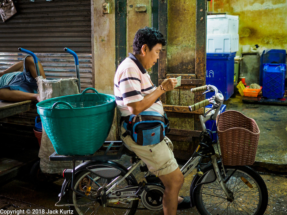 31 JULY 2018 - BANGKOK, THAILAND: A woman shopping on her bicycle counts her cash in an alley in Bangkok's Chinatown district, one of the largest Chinatowns in the world. It was established in 1781 when Siamese King Rama I gave the Chinese community in Bangkok land outside of Bangkok's city walls so he could build his palace (what is now known as the Grand Palace). Chinatown is now the heart of the Thai-Chinese community. About 14% of Thais have Chinese ancestry.    PHOTO BY JACK KURTZ