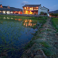 The lights of the Heshun Renjia restaurant across the rice paddies on the edge of the ancient city. Heshun was chosen as the most charming town in China by CCTV (China Central Television) in 2006. The town was founded over 600 years ago when the emperor ordered soldiers, mostly from Sichuan, to move to this area to guard the Ancient Southwest Silk Route, a trading route that extended from Chengdu, China to India. The route enabled traders to transport silk and tea via horse caravan from China to Myanmar and India, and return with jade and gems.
