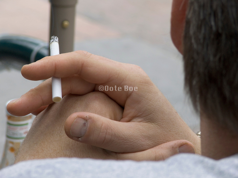 close up man holding a cigarette between his fingers