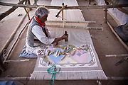 A hindu man weaves a dhurrie (carpet) in the back yard of his house in a village noted for dhurrie making, Salawas, Rajasthan, India