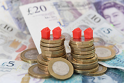 File photo dated 12/09/18 of model houses on a pile of coins and bank notes, as the number of people in Scotland who are struggling to pay for their home has increased by nearly a third in the last two years, according to a study.