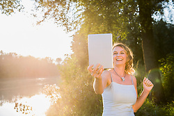 Cheerful woman smiling while using digital tablet at riverbank, Bavaria, Germany